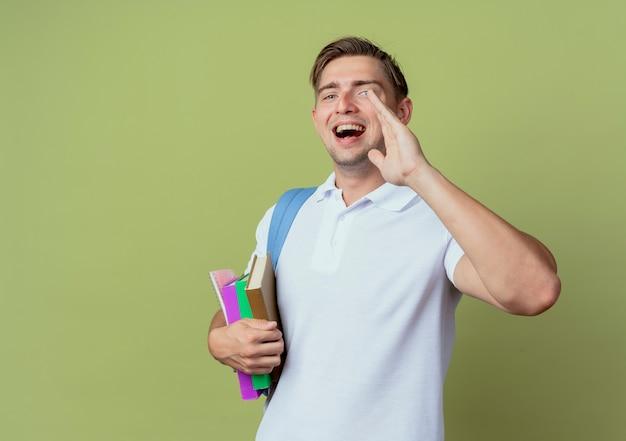 Kijkend naar de camera vrolijke jonge knappe mannelijke student die rugtas draagt die boeken houdt en iemand belt die op olijfgroene achtergrond wordt geïsoleerd
