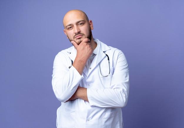Kijkend naar de camera zelfverzekerde jonge kale mannelijke arts dragen medische gewaad en stethoscoop hand op kin geïsoleerd op blauwe achtergrond met kopie ruimte