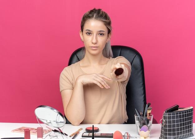 Kijkend naar de camera zit een mooi meisje aan tafel met make-uptools die een poederborstel vasthouden die op een roze muur is geïsoleerd
