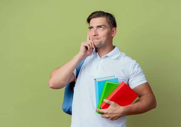 Kijkend naar de denkende jonge knappe mannelijke student die rugtas draagt die boeken houdt en hand op wang zet die op olijfgroene achtergrond wordt geïsoleerd