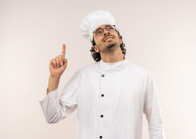 Kijkend naar de glimlachende jonge mannelijke kok die eenvormige chef-kok draagt en glazen wijst naar kant