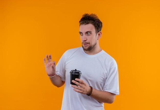 Kijkend naar de jonge kerel aan de zijkant die een wit t-shirt draagt en een kopje koffie houdt dat goed gebaar op geïsoleerde oranje achtergrond toont