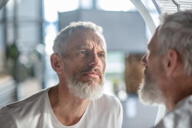 Kijkend naar de reflectie. een bebaarde grijsharige man die in de spiegel kijkt