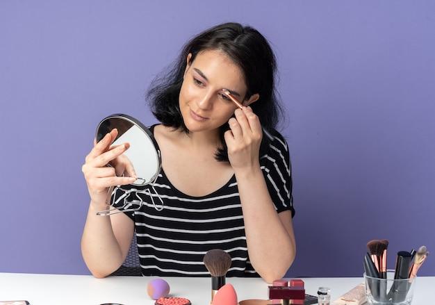 Kijkend naar de spiegel, een blij kijkend jong mooi meisje zit aan tafel met make-uptools die oogschaduw aanbrengen met een make-upborstel geïsoleerd op een blauwe muur