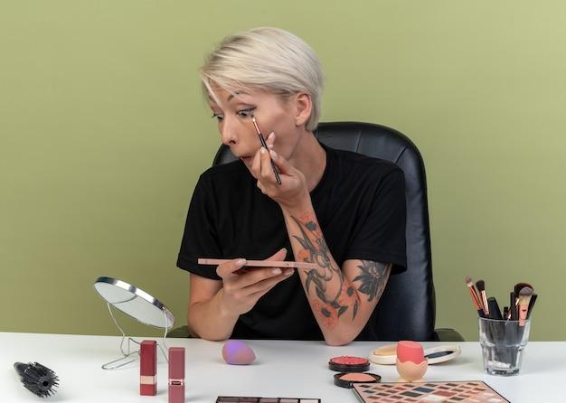 Kijkend naar de spiegel zit een mooi meisje aan tafel met make-uptools die oogschaduw toepassen met make-upborstels die op een olijfgroene muur zijn geïsoleerd
