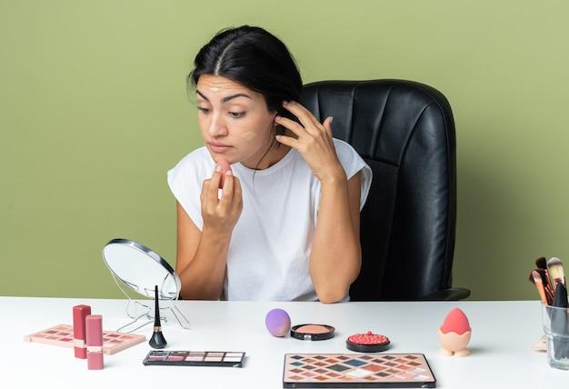 Kijkend naar de spiegel zit een mooie vrouw aan tafel met make-uptools die tooncrème met spons toepast