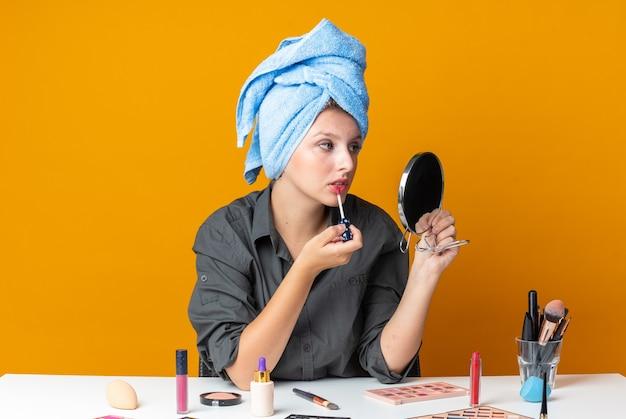 Kijkend naar de spiegel zit een mooie vrouw aan tafel met make-uptools gewikkeld haar in een handdoek die lipgloss aanbrengt