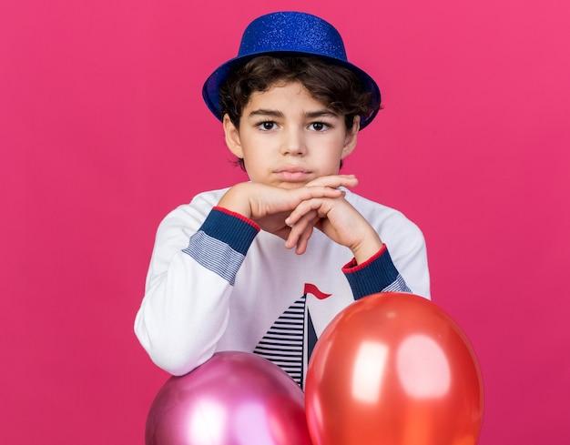 Kijkend naar de voorkant van een kleine jongen met een blauwe feesthoed die achter ballonnen staat en elkaars hand vasthoudt, geïsoleerd op een roze muur