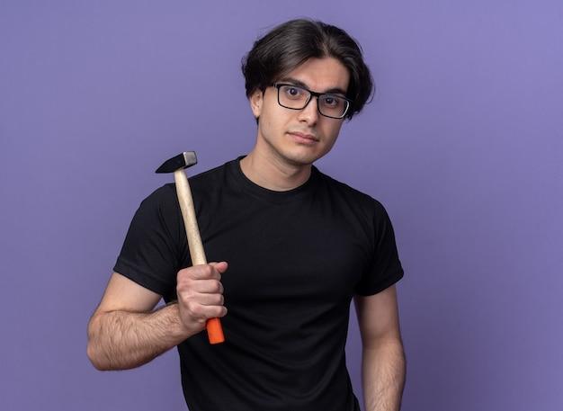 Kijkend naar de voorste jonge knappe kerel die zwart t-shirt en bril draagt die hamer op schouder zet die op purpere muur wordt geïsoleerd