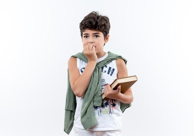 Kijkend naar de zijkant betrokken kleine schooljongen die boek vasthoudt en nagels bijt