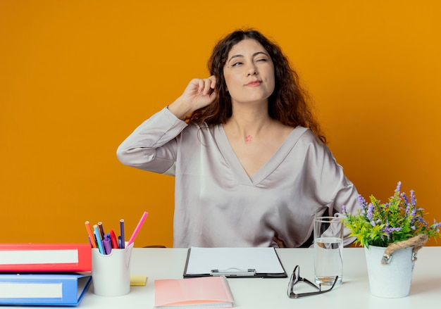 Kijkend naar de zijkant, denkend aan een jonge, mooie vrouwelijke kantoormedewerker die aan een bureau zit