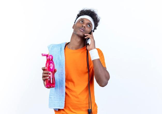 Kijkend naar de zijkant, denkende jonge afro-amerikaanse sportieve man met hoofdband en polsbandje spreekt op telefoon met waterfles met handdoek en springtouw op schouder