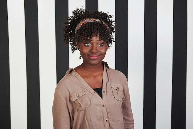 Kijkend naar de zijkant. glimlachte afro-amerikaanse meisje staat in de studio met verticale witte en zwarte lijnen op de achtergrond