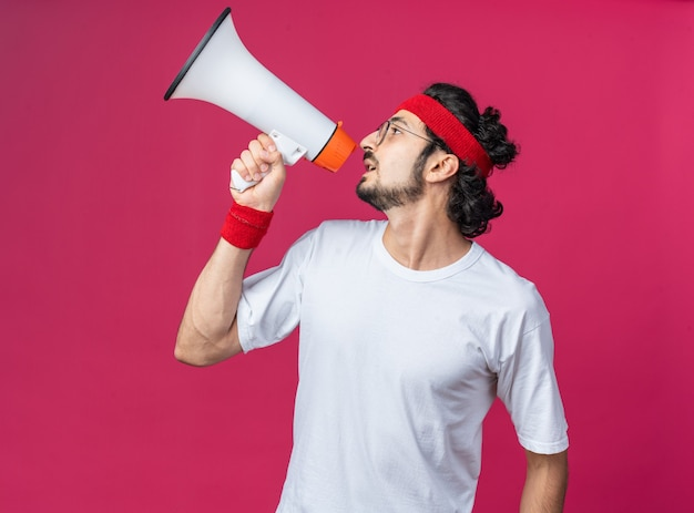 Kijkend naar de zijkant, jonge sportieve man met hoofdband met polsbandje spreekt op luidspreker