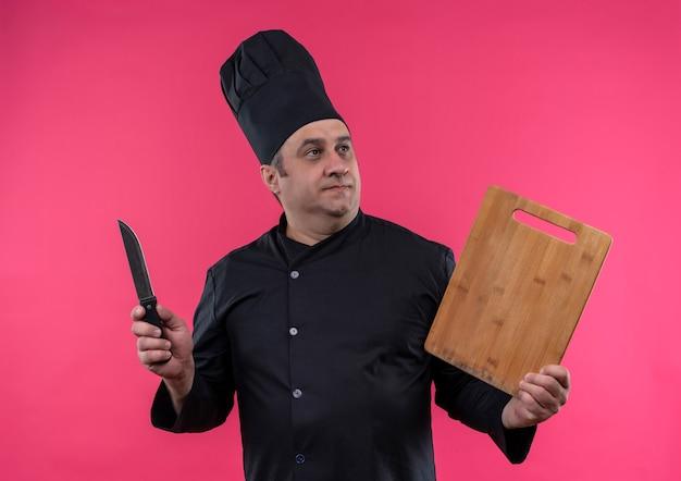 Kijkend naar de zijkant mannelijke kok van middelbare leeftijd in chef-kok uniform met snijplank en mes op geïsoleerde roze muur
