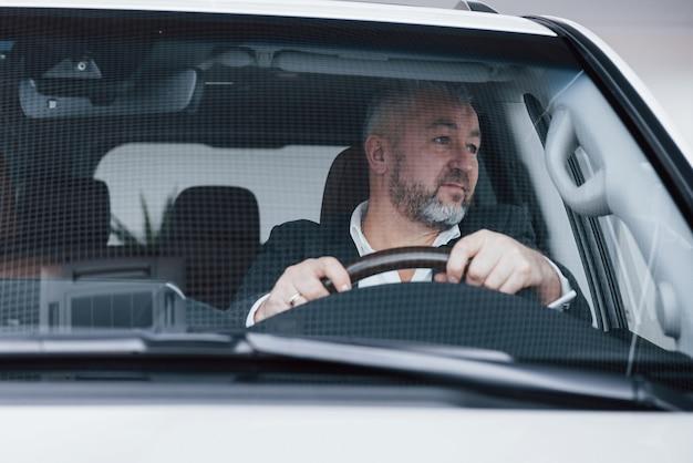Kijkend naar de zijkant. vooraanzicht van hogere zakenman in zijn nieuwe moderne auto die nieuwe functies test
