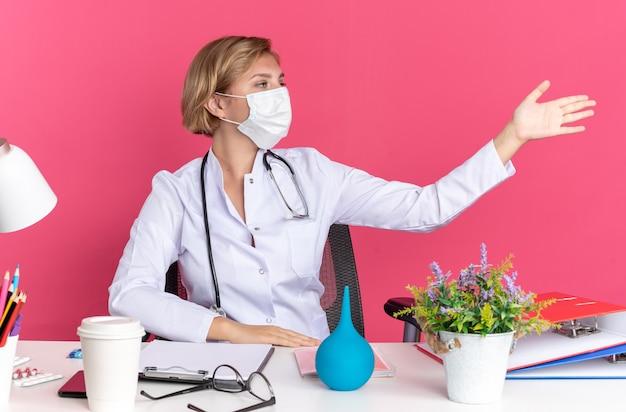Kijkend naar de zijkant zit een jonge vrouwelijke arts met een medisch gewaad met een stethoscoop en een masker aan een bureau met medische hulpmiddelen wijst met de hand aan de zijkant geïsoleerd op roze muur
