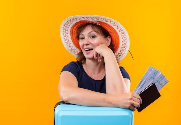 Kijkend naar de zijreizigervrouw van middelbare leeftijd in de kaartjes en de portefeuille van de hoedenholding die hand op koffer op geïsoleerde gele muur zetten