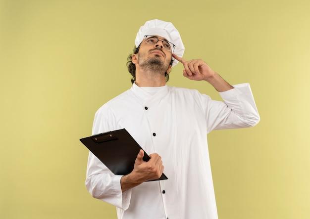 Kijkend naar denkende jonge mannelijke kok die eenvormige chef-kok en glazen draagt die klembord houdt en vinger op voorhoofd zet