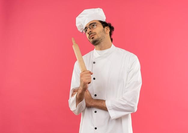 Kijkend naar denkende jonge mannelijke kok die eenvormige chef-kok en glazen draagt die rollende pan houdt