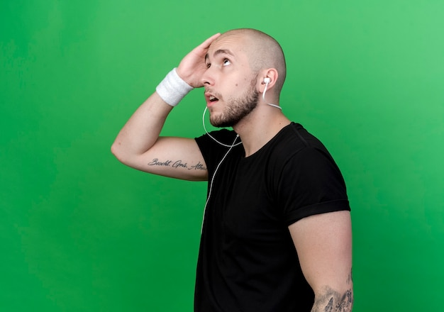 Kijkend naar denkende jonge sportieve man met polsbandje hand op voorhoofd zetten geïsoleerd op groene muur