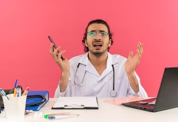 Kijkend naar een bezorgde jonge mannelijke arts met een medische bril die een medisch gewaad draagt met een stethoscoop die aan het bureau zit