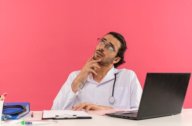 Kijkend naar een denkende jonge mannelijke arts met een medische bril die een medisch gewaad draagt met een stethoscoop die aan het bureau zit