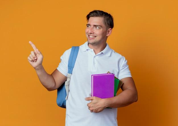 Kijkend naar een glimlachende jonge knappe mannelijke student die een rugtas draagt met boeken en punten aan de zijkant