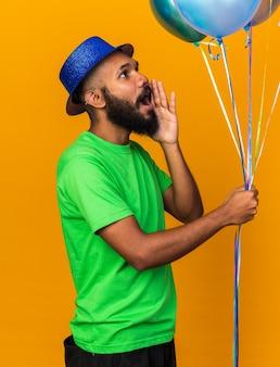Kijkend naar een jonge afro-amerikaanse man met een feesthoed die ballonnen vasthoudt en iemand belt die op een oranje muur is geïsoleerd