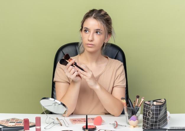 Kijkend naar een jonge, mooie meid die aan een bureau zit met make-uphulpmiddelen die een make-upborstel op een olijfgroene muur houden