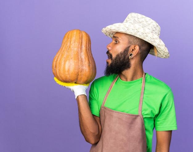 Kijkend naar een jonge tuinman, een afro-amerikaanse man met een tuinhoed en handschoenen met pompoen
