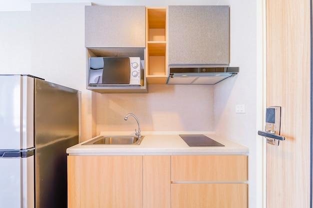 Kijkend naar een kleine lege keuken met fornuis, koelkast en kasten