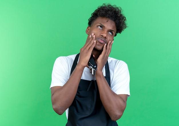 Kijkend naar een trieste jonge afro-amerikaanse mannelijke kapper die een uniform draagt met een tondeuse en handen op de wangen legt
