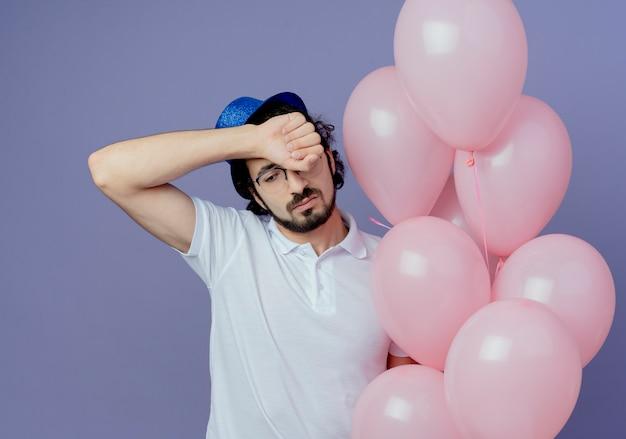 Kijkend naar een trieste knappe man met een bril en een blauwe hoed die ballonnen vasthoudt en een pols op het voorhoofd zet