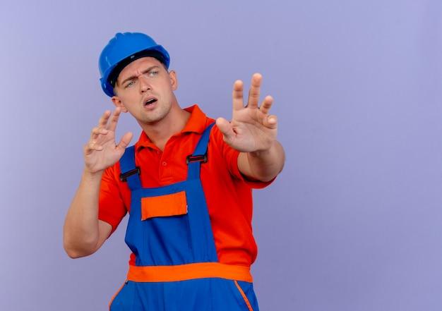 Kijkend naar een verwarde jonge mannelijke bouwer die een uniform draagt en een veiligheidshelm die handen uitsteekt