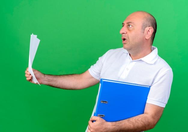 Kijkend naar kant bang casual volwassen man met map met papier geïsoleerd op een groene achtergrond