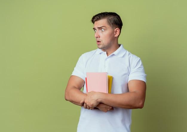 Kijkend naar kant bang jonge knappe mannelijke student met boeken geïsoleerd op olijfgroene achtergrond