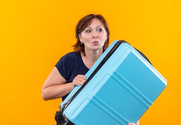 Kijkend naar kant betrokken reiziger vrouw met koffer op middelbare leeftijd
