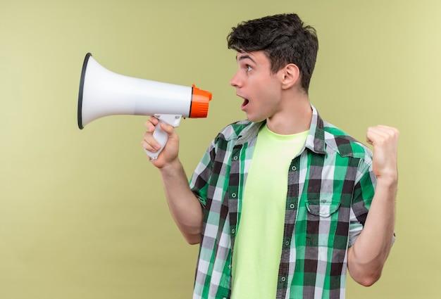 Kijkend naar kant blanke jongeman met groen shirt spreekt door luidspreker met ja gebaar op geïsoleerde groene muur