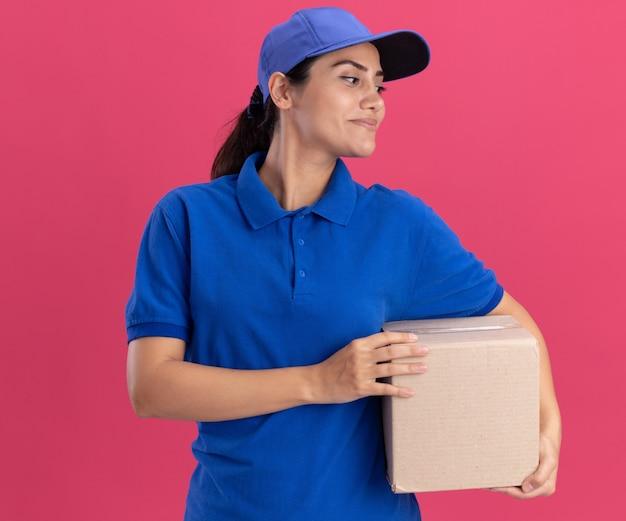 Kijkend naar kant blij jong leveringsmeisje die uniform met de doos van de glbholding dragen die op roze muur wordt geïsoleerd
