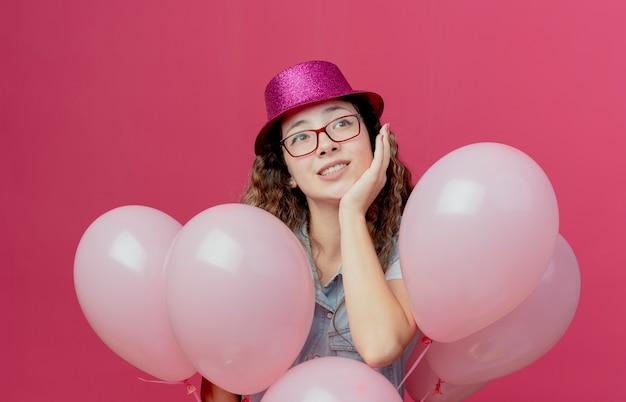Kijkend naar kant blij jong meisje met bril en roze hoed staande achter ballonnen en hand op wang geïsoleerd op roze achtergrond