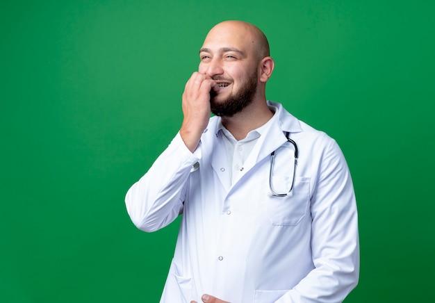 Kijkend naar kant blij jonge mannelijke arts dragen medische gewaad en stethoscoop bijt nagels geïsoleerd op groene achtergrond