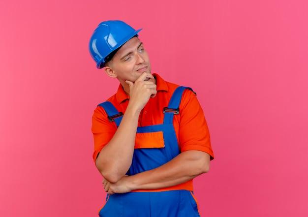 Kijkend naar kant blij jonge mannelijke bouwer dragen uniform en veiligheidshelm zetten hand onder de kin
