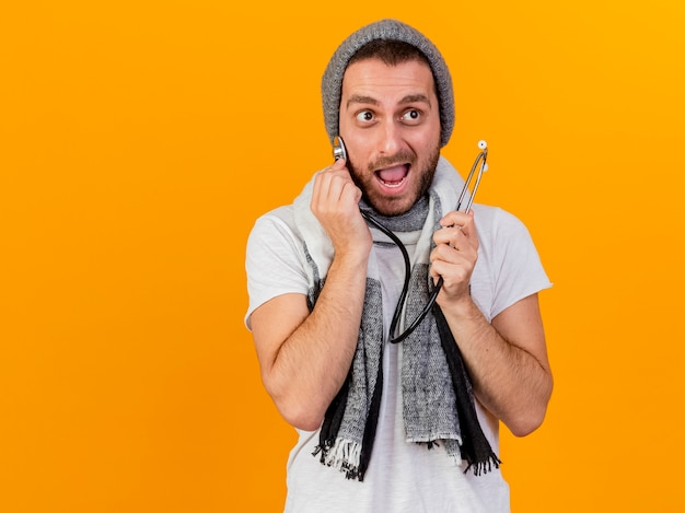 Kijkend naar kant blije jonge zieke man met winter hoed en sjaal houden en stethoscoop zetten wang geïsoleerd op geel