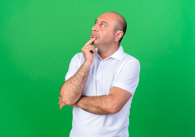 Kijkend naar kant denken casual volwassen man hand onder de kin zetten geïsoleerd op groene muur