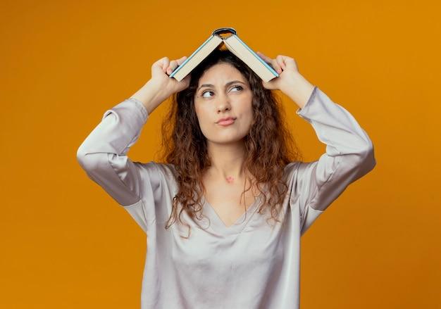 Kijkend naar kant denken jong mooi meisje bedekt hoofd met boek geïsoleerd op gele achtergrond