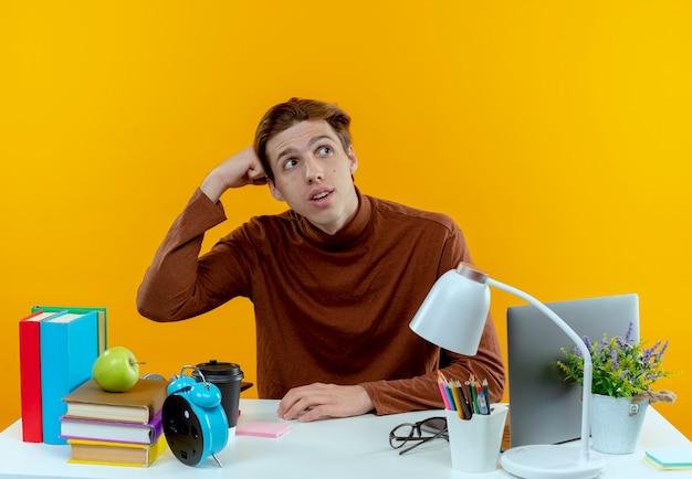 Kijkend naar kant denken jonge student jongen zit aan bureau met school tools vuist op hoofd zetten
