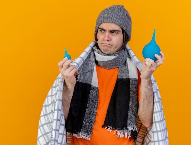 Kijkend naar kant denken jonge zieke man met winter hoed met sjaal verpakt in plaid bedrijf klysma's geïsoleerd op een oranje achtergrond