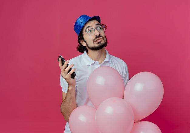 Kijkend naar kant denken knappe man met bril en blauwe hoed met ballonnen en telefoon geïsoleerd op roze achtergrond