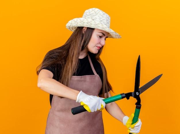 Kijkend naar kant denken mooie tuinman meisje dragen uniform en tuinieren hoed met handschoenen stak tondeuse aan kant geïsoleerd op een oranje achtergrond